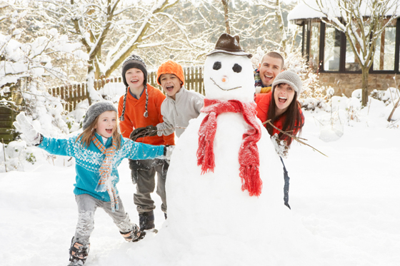 Family having fun building snowman in garden © iStockphoto