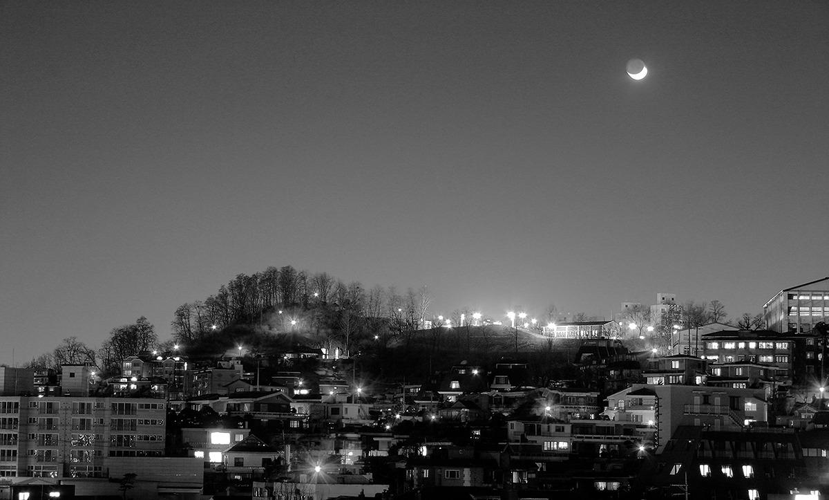 눈썹달이 떠 있고 그 밑으로 산 등성에 집들의 불빛이 다닥다닥 붙어보이는 사진.